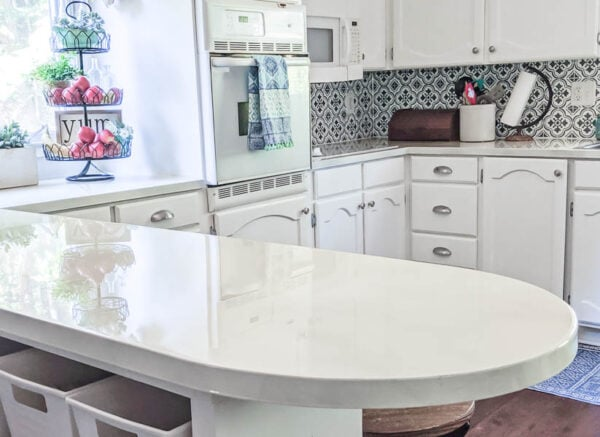 Kitchen updated with painted white countertops, white painted cabinets, and a stenciled backsplash