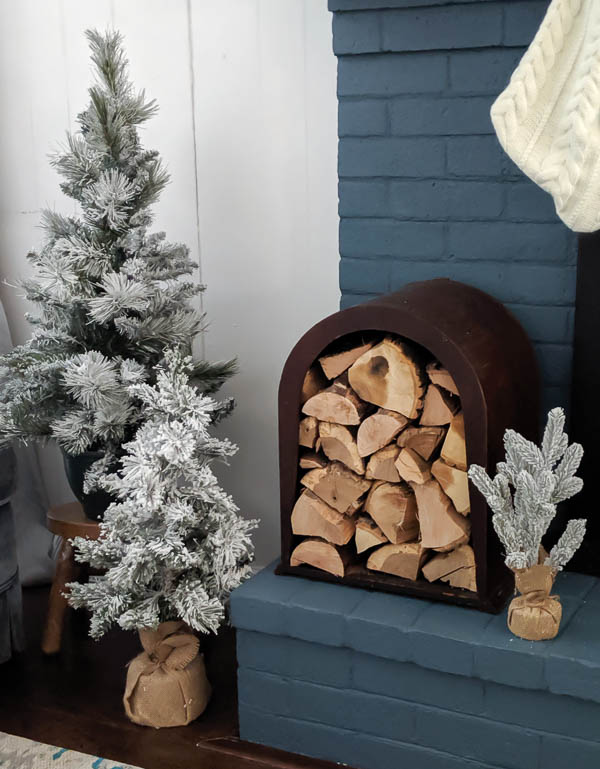 Cozy neutral Christmas fireplace with flocked Christmas trees, a unique firewood holder, and pretty white knit stockings.