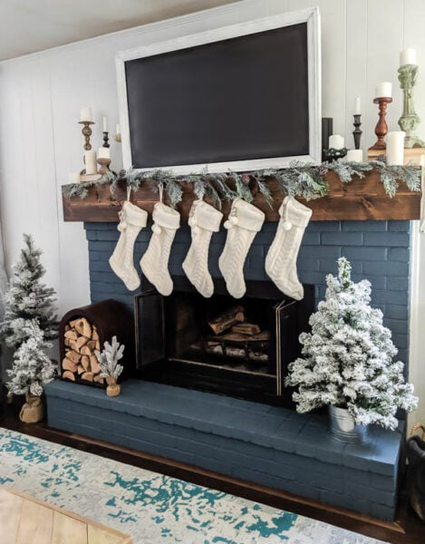This neutral Christmas fireplace is full of beautiful Christmas touches including mini flocked Christmas trees, a unique firewood holder, and cable knit stockings.