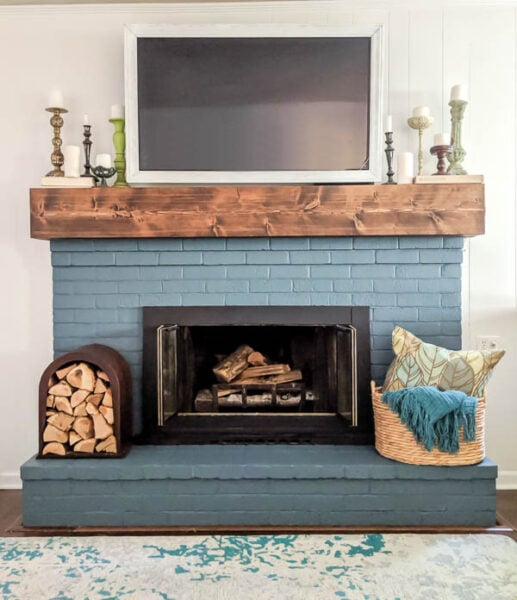 DIY fireplace facelift with painted blue brick, DIY chunky wood mantel, DIY TV frame, and upcycled firewood holder.