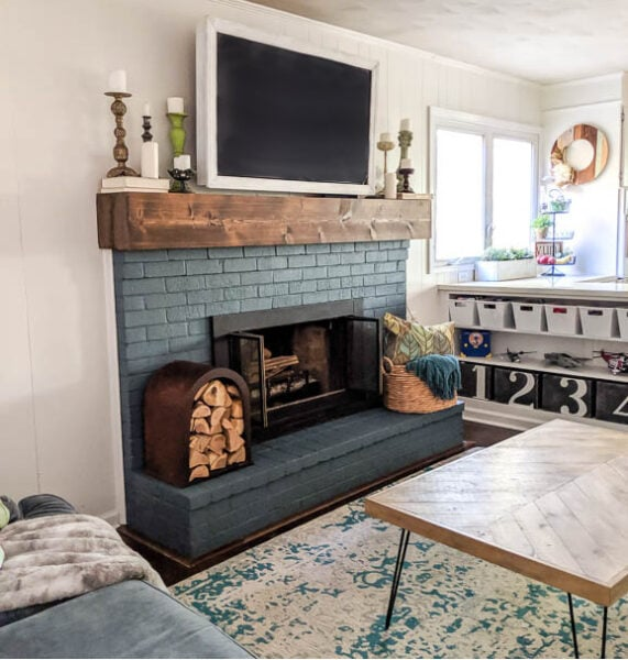 Navy fireplace with chunky DIY mantel and upcycled firewood holder. This whole room is full of DIY and upcycled projects.