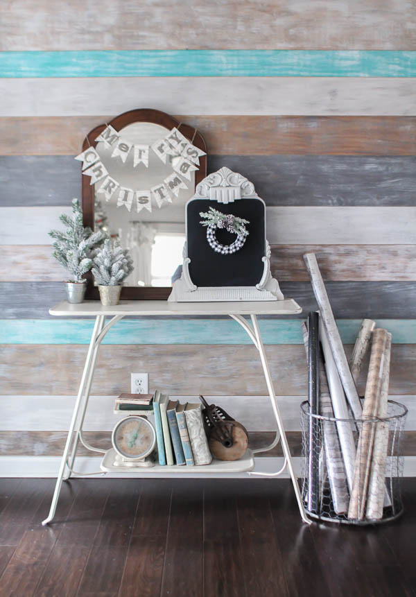 Entryway with weathered wood plank wall and white table with old mirrors, Merry Christmas sign, and mini Christmas trees next to basket of wrapping paper.