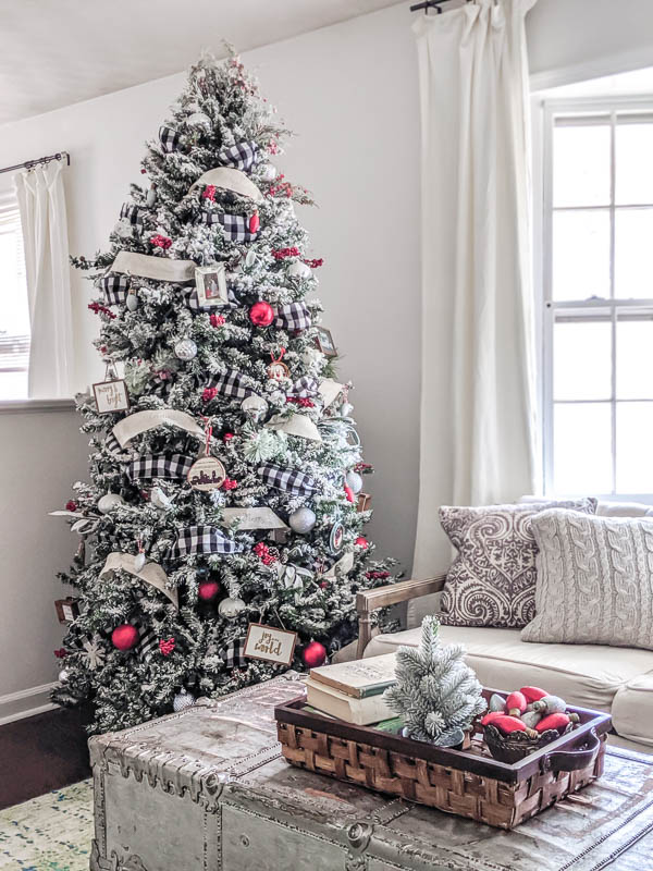 Classic Farmhouse Christmas tree with buffalo plaid ribbon, red berries and pinecones, and lots of handmade farmhouse ornaments. There are lots of ideas in this post for creating your own farmhouse Christmas tree on a budget.