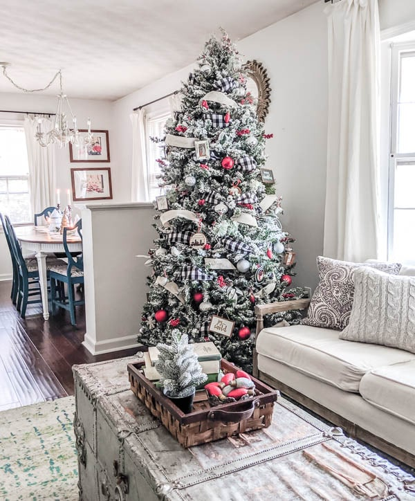 I love how cheerful this red and white farmhouse Christmas tree is. With lots of DIY ornament ideas, DIY flocking, and buffalo plaid ribbon, this tree has just the right amount of farmhouse style without becoming cliche.