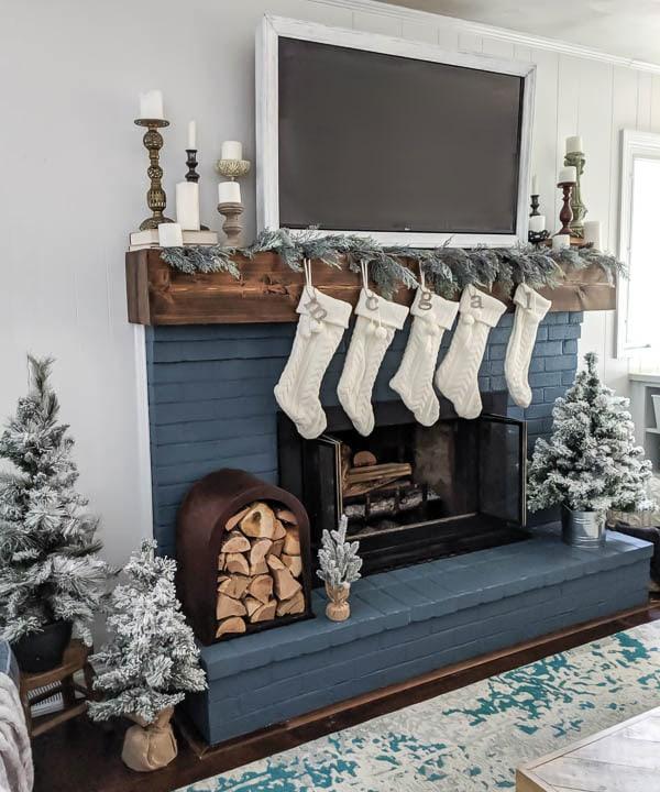 Garland, white Christmas stockings, pillar candles, and mini Christmas trees around brick fireplace.
