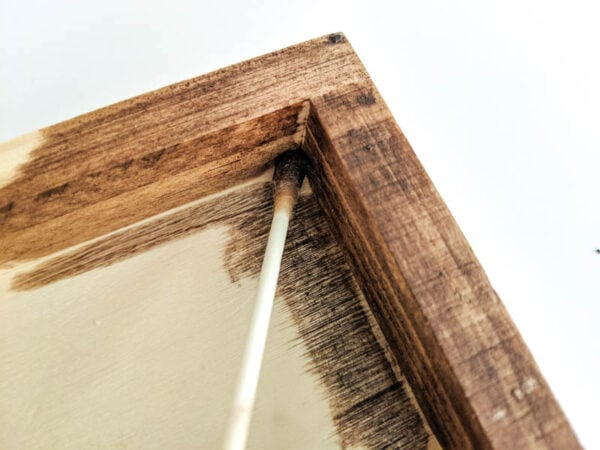 using a q-tip to get stain into the small interior corners of the frame.