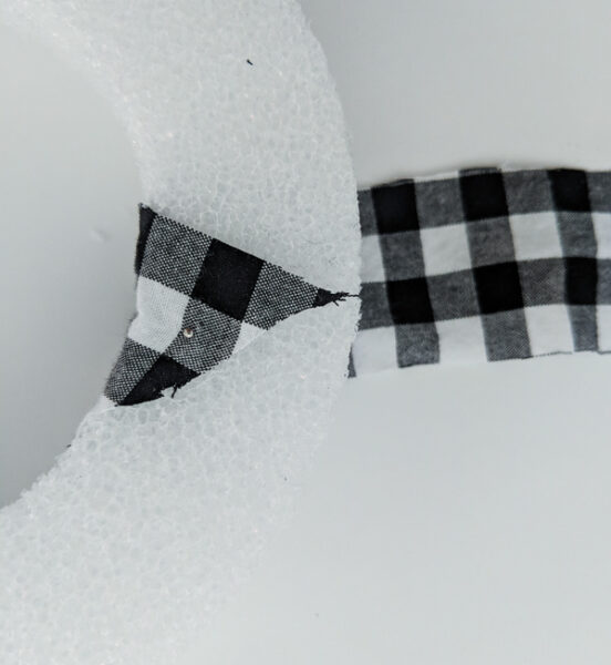 wrapping a strip of plaid fabric around the wreath form and pinning it to the form with a straight pin.