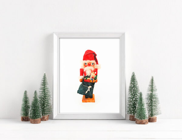 Framed Santa nutcracker art print surrounded by bottle brush Christmas trees.