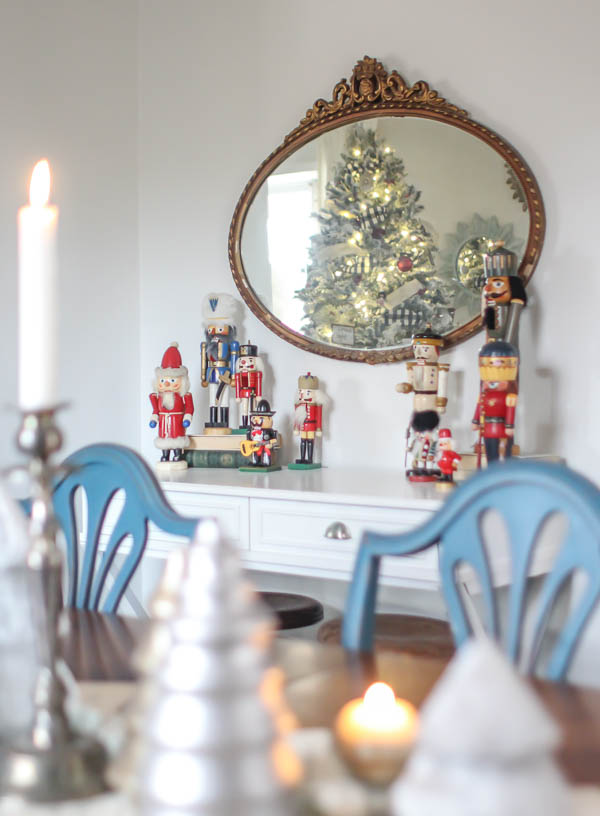 A collection of nutcrackers on a small table surrounded by other Christmas decor.
