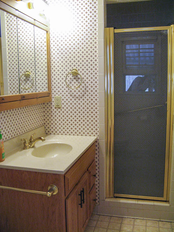 dated bathroom with gold fixtures and wallpaper