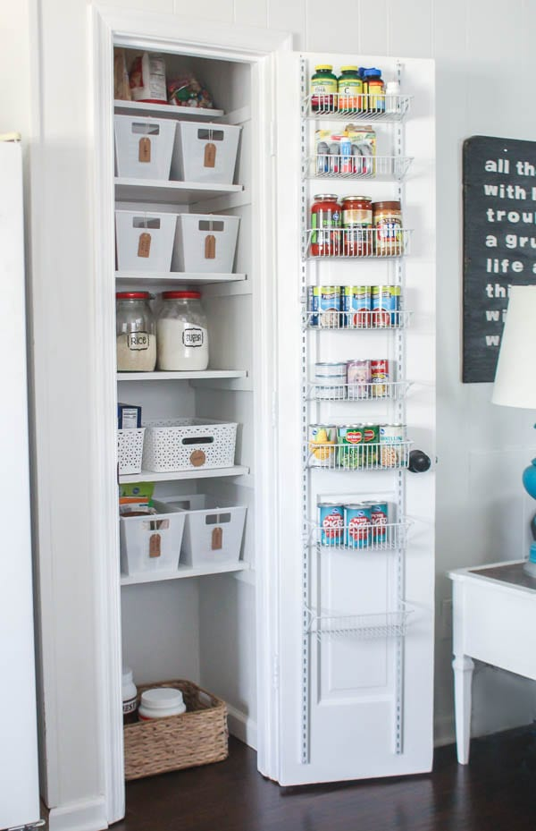 small pantry closet with behind the door shelves and baskets and jars for organization