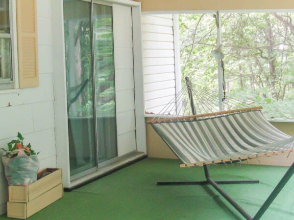 ugly screened-in porch with green astroturf carpet and peach paint