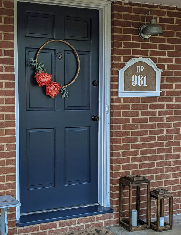 diy house number on front porch with navy front door and brick walls