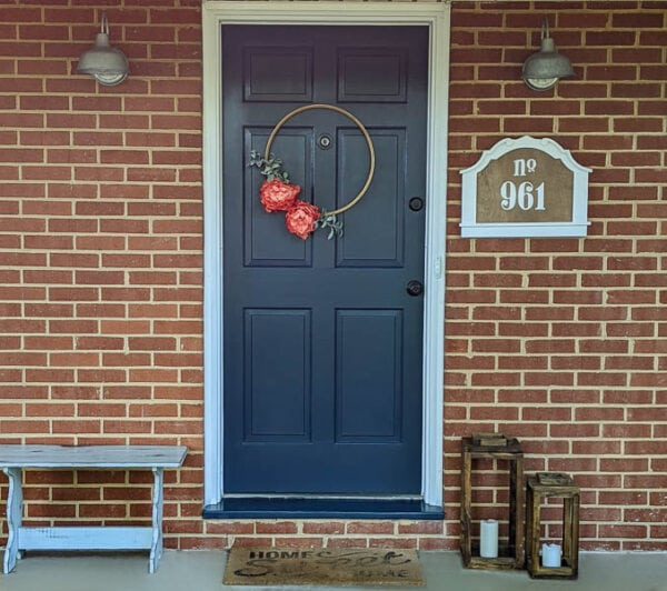 front porch of brick ranch home with navy front door, diy house number, and embroidery hoop wreath