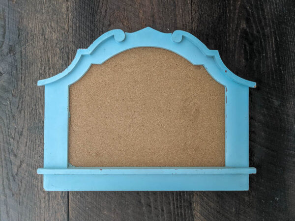 blue framed corkboard with an interesting arched shape