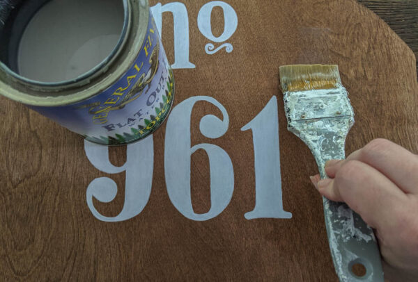 painting sealer onto plywood house number with a paintbrush