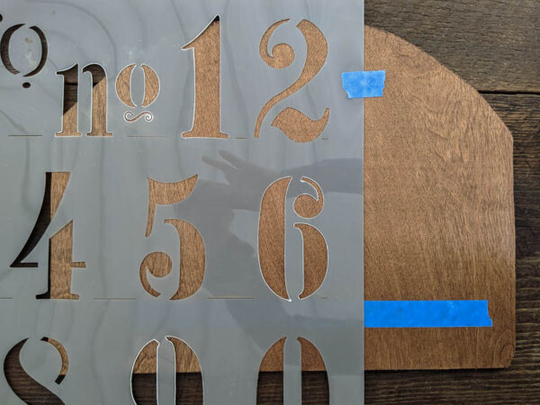 stenciling the house numbers onto the plywood