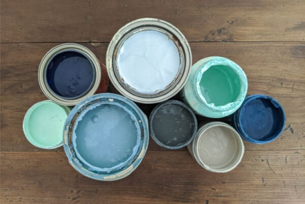 Eight different cans of furniture paint open to share the paint inside.