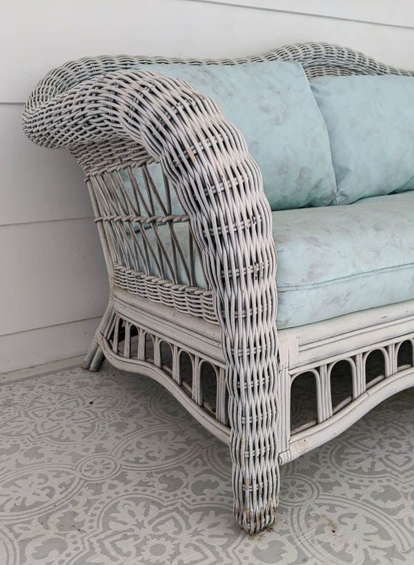 close up of white wicker sofa with dingy, peeling paint
