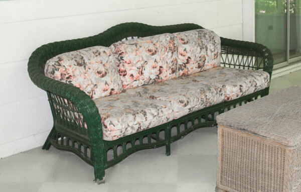 green wicker couch with pink floral cushions