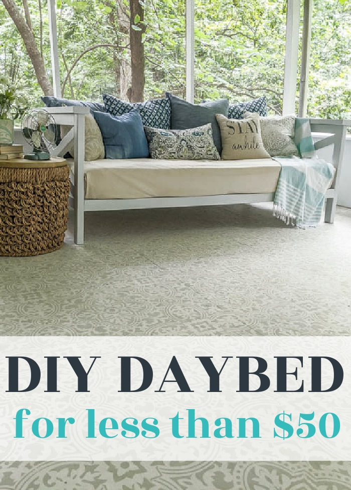 diy wooden daybed on a porch with pillows and basket side table