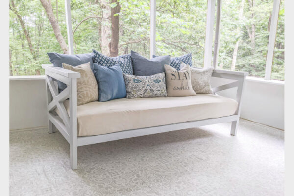 diy wooden daybed on screened-in porch.