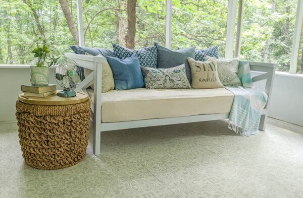 daybed filled with pillows and a throw blanket with a woven basket table next to it