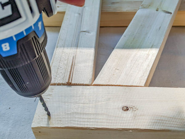 predrilling holes in side of daybed with drill.