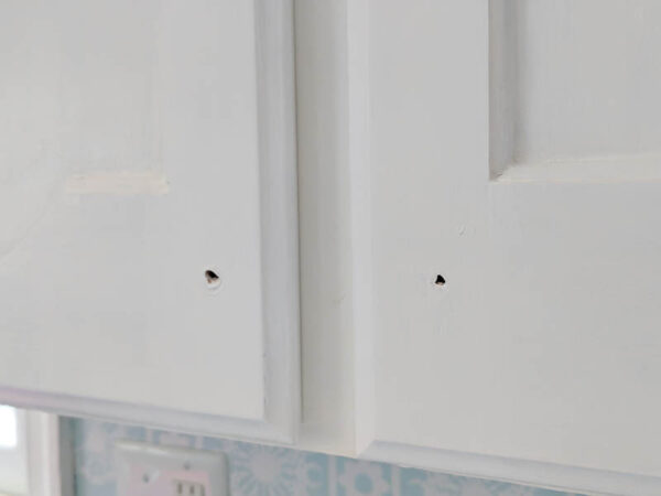 close up of fresh white paint on cabinet doors after touching up the chipped paint