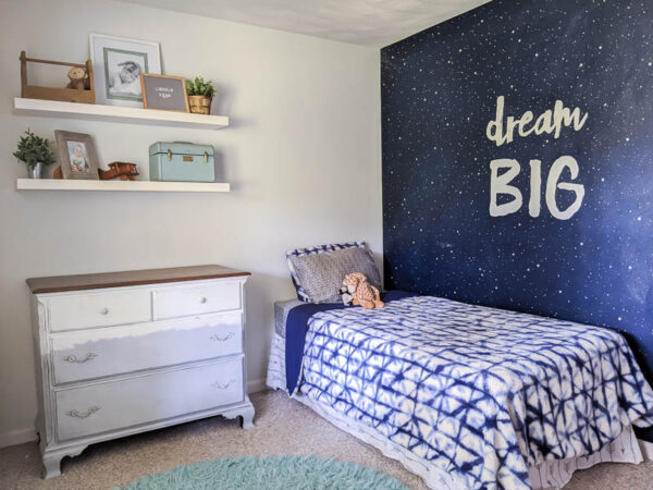 Boy bedroom with blue and white shibori blanket and navy star wall.