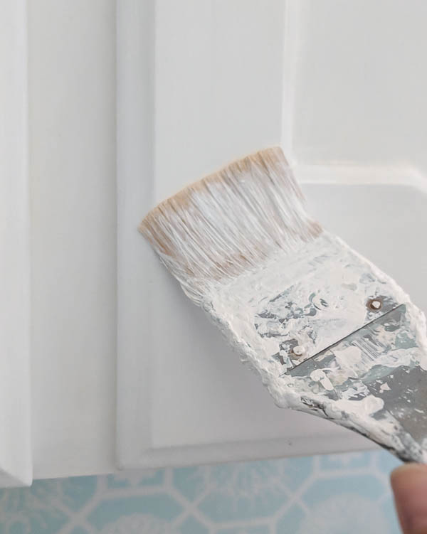 touching up cabinet paint with a small paintbrush