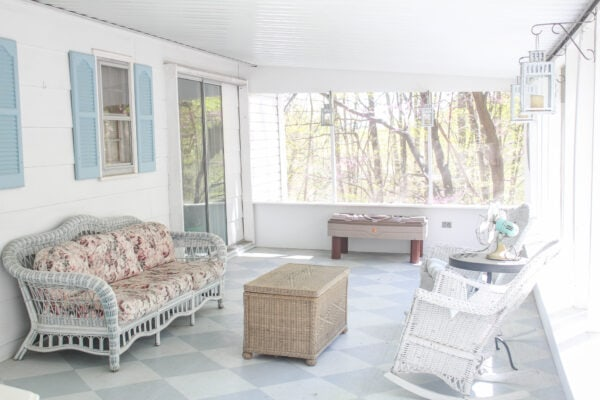 screened-in porch with painted checkerboard floor and wicker furniture