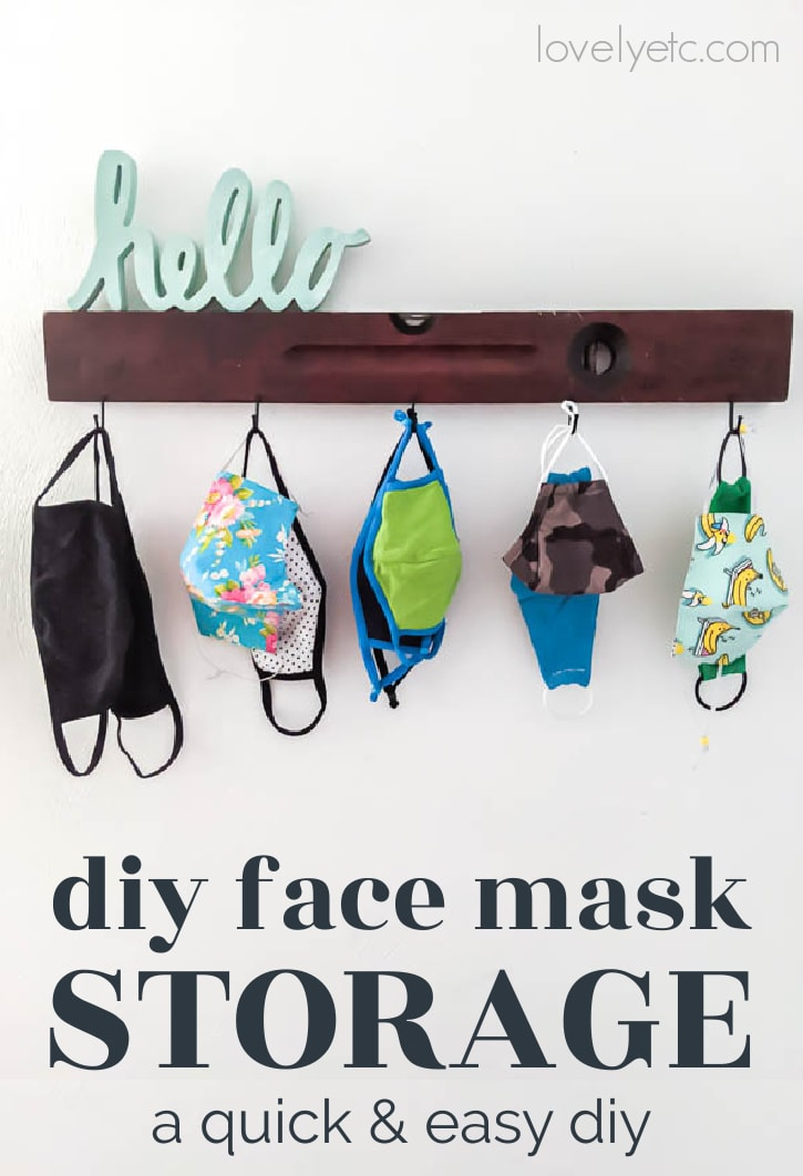 face masks for the whole family stored on wall hooks next to the front door with a cute hello sign above