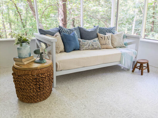 diy wood daybed on porch with drop cloth cover and lots of pillows