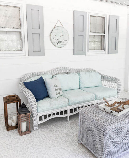 white wicker couch with painted cushions on white screened in porch with gray shutters
