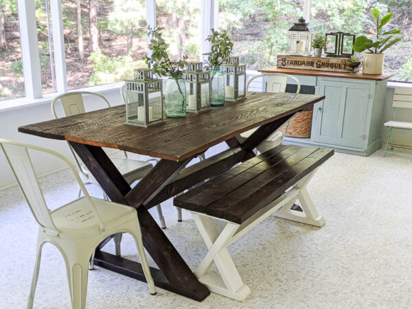 dark wood farmhouse table with wood bench and white bistro chairs on porch