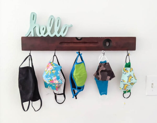 wall hook mask organizer with masks of different sizes hanging from the hooks
