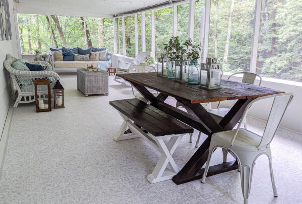 large screened in porch with stenciled floor, white wicker furniture, wooden dining table, and daybed