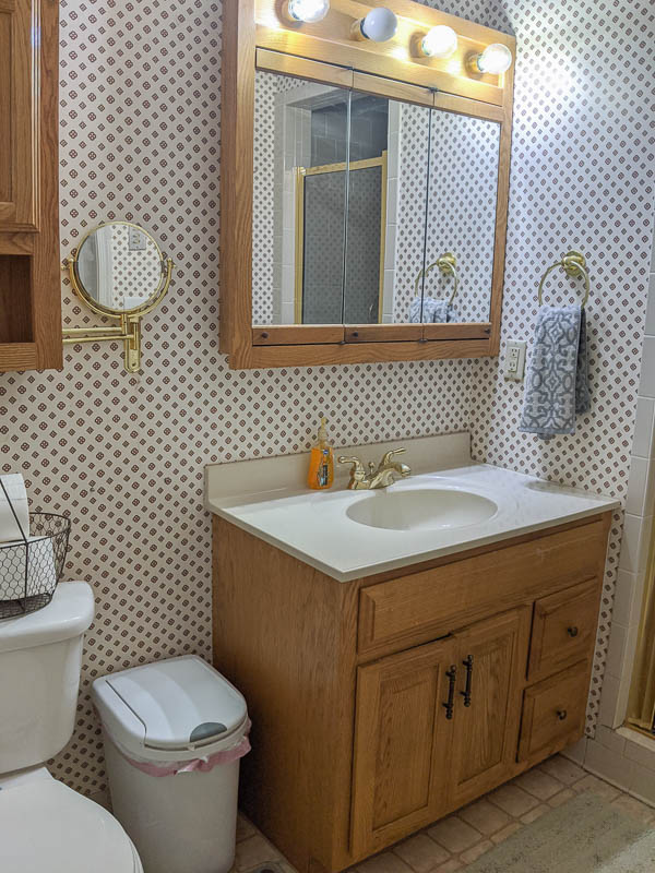 dated bathroom with busy wallpaper, oak vanity, huge oak medicine cabinet with attached light, and gold fixtures