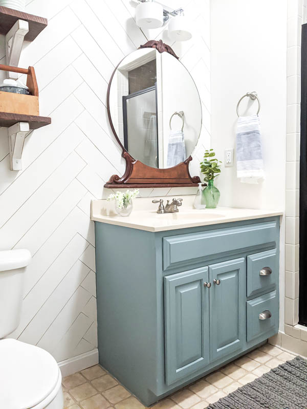 bathroom after $100 remodel with painted blue vanity, vintage mirror, and herringbone wood wall