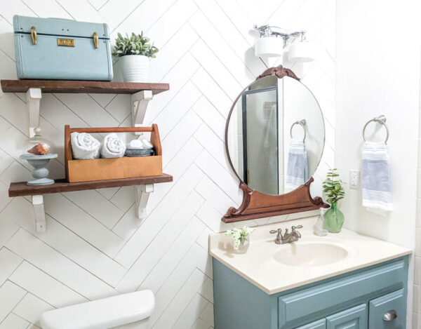 small bathroom with white herringbone shiplap wall, open shelves, and vintage wood mirror
