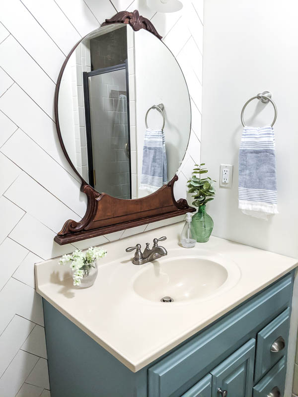 Painted blue vanity and vintage wood mirror against white wood wall