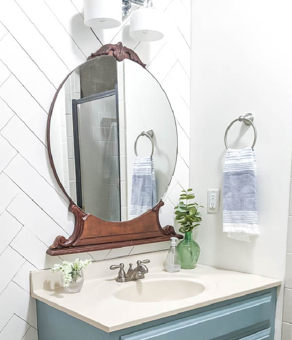 Large round vintage mirror from an old dresser hangs above the painted bathroom vanity.