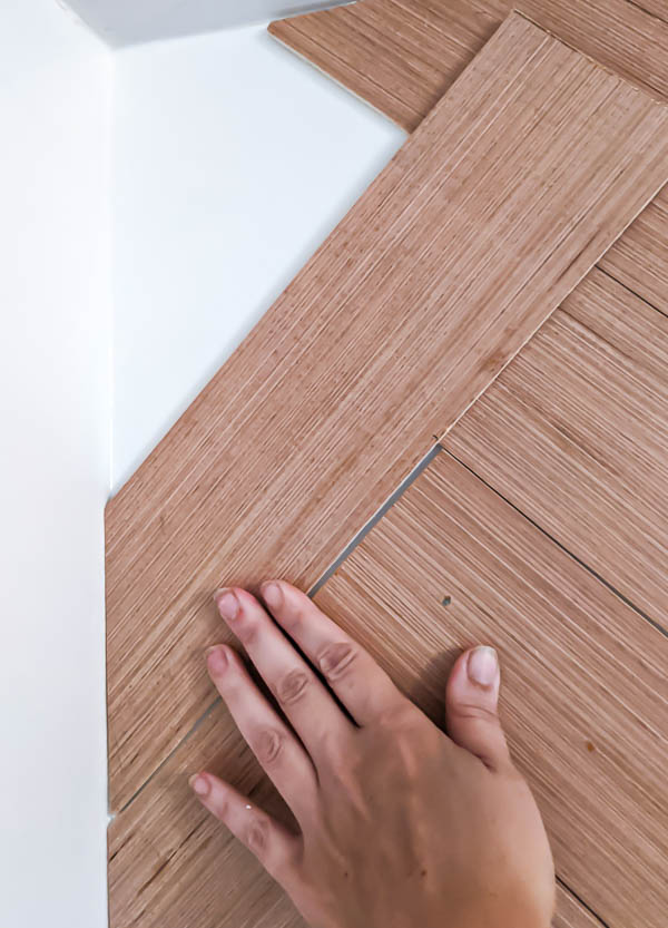 Measuring a plank against the wall to determine where to cut.