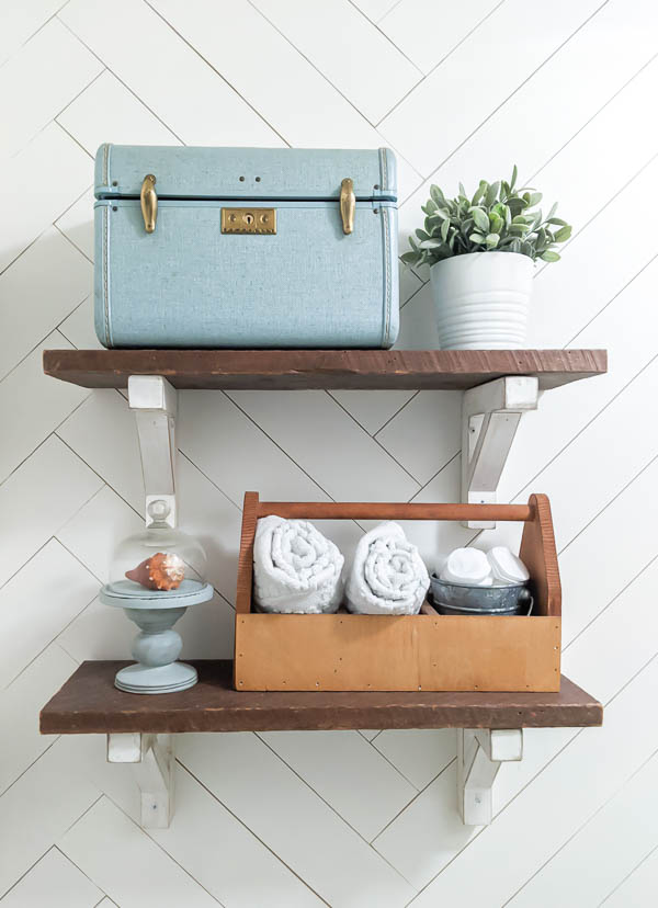 Open shelving over toilet with a small suitcase and wooden tool tote for storage and a small plant and cloche to accessorize.