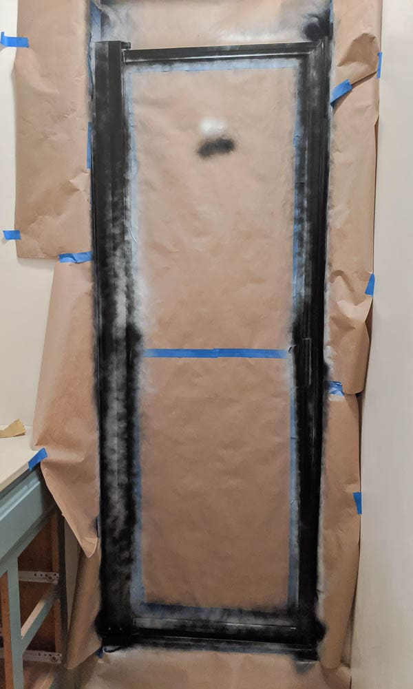 metal shower door frame spray painted black after first layer of black paint
