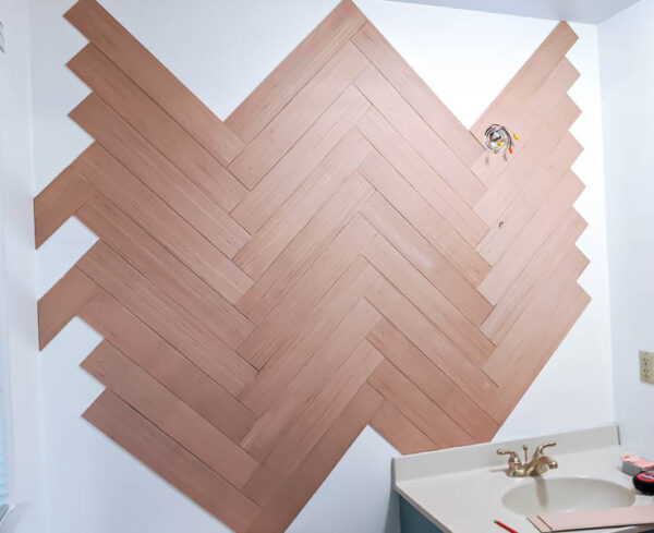 partially finished herringbone wood wall with empty spaces all along the edges where wood hasn't been added yet.
