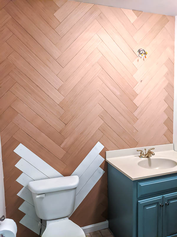 Completed herringbone wood wall with a few pieces of wood painted white behind the toilet.