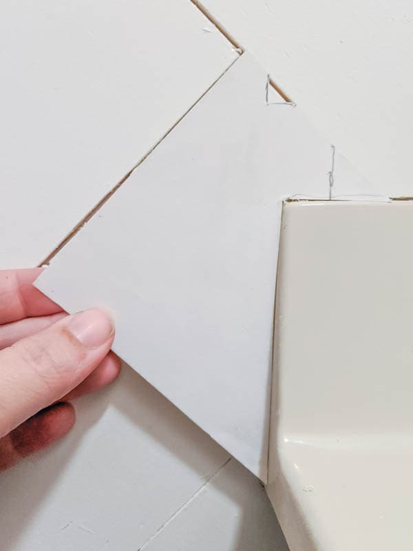 Holding a paper pattern against the corner of the vanity in the shape the wood plank needs to be cut.