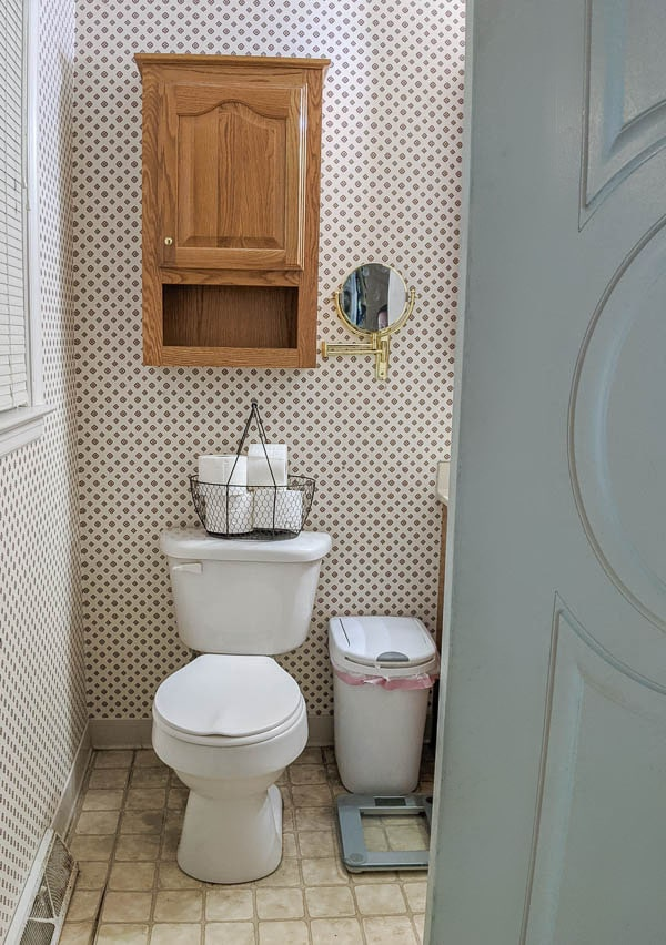 small bathroom with wallpaper with a diamond pattern, vinyl floors, and a big cabinet over the toilet.
